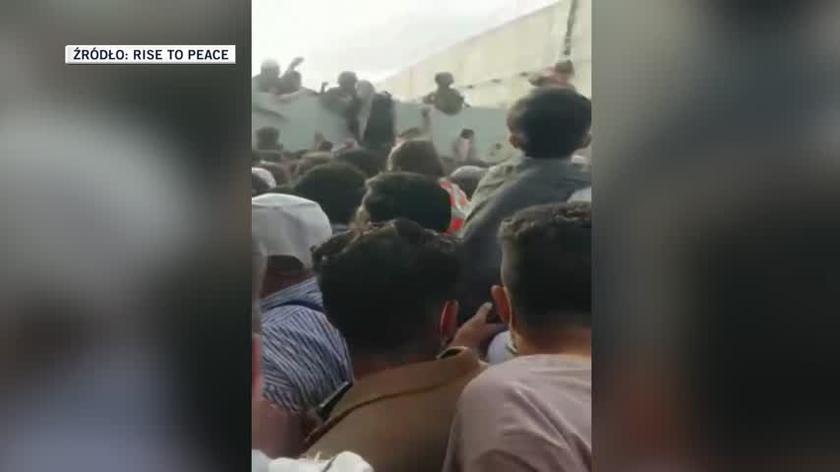 Żołnierze pomagają afgańskiej kobiecie przedostać się na mur przy lotnisku w Kabulu