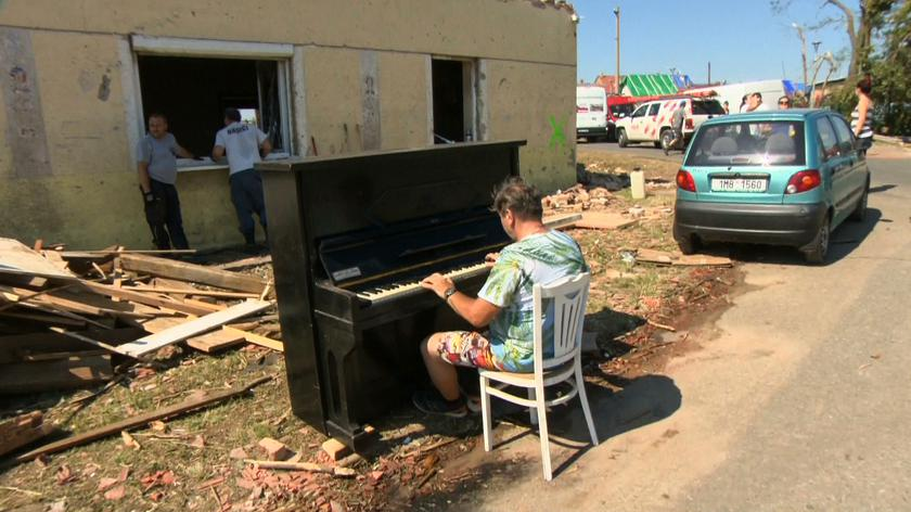 Gra na pianinie przed zniszczonym domem