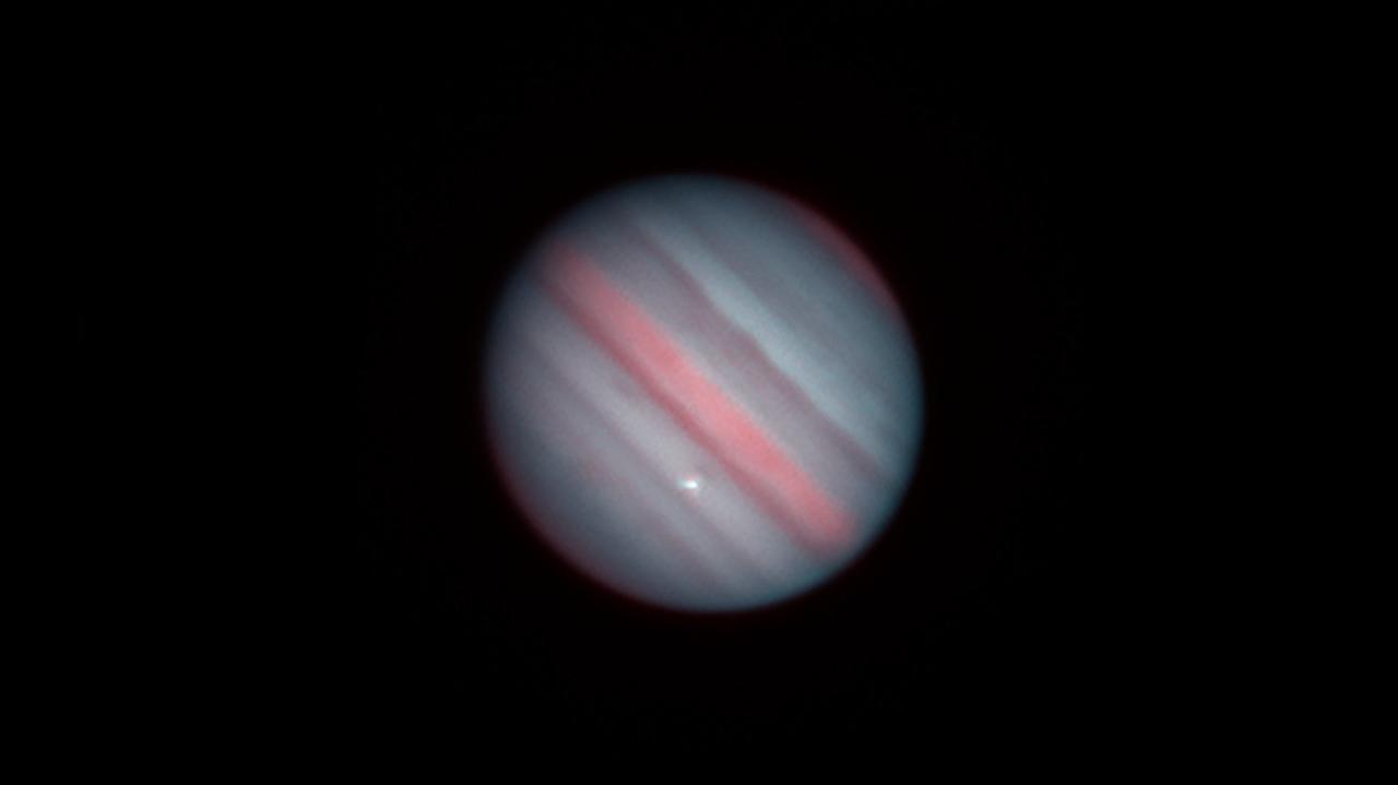 Jowisz uderzony przez kosmiczny obiekt. Jasny błysk widać na zdjęciu